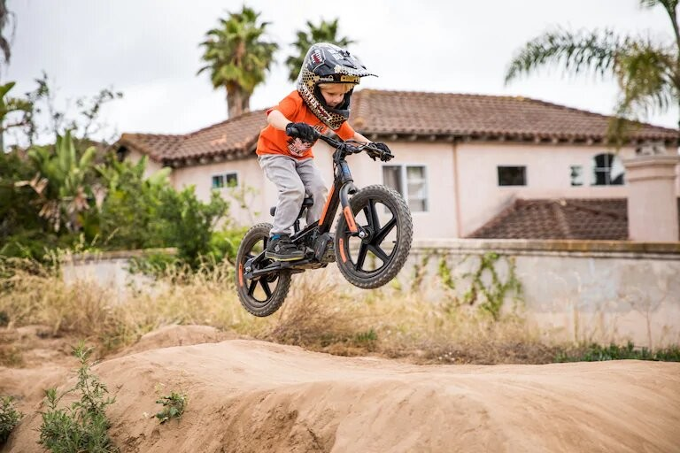 Child jumping with an electric dirt balance bike.
