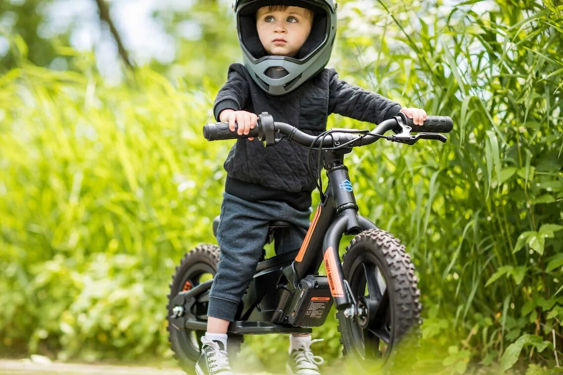 Boy riding Harley Davidson Electric Balance Bike in a field