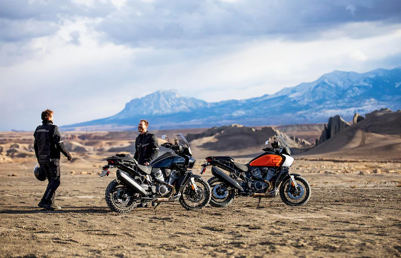 Two riders with Harley-Davidson Pan America adventure touring motorcycle greeting one another in the desert