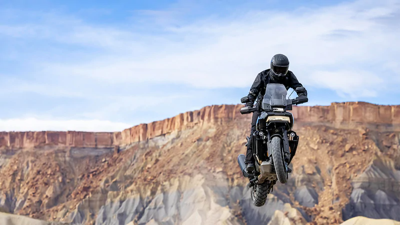 Driver jumping off the dirt on a Harley Davidson Pan America™ Touring motorcycle